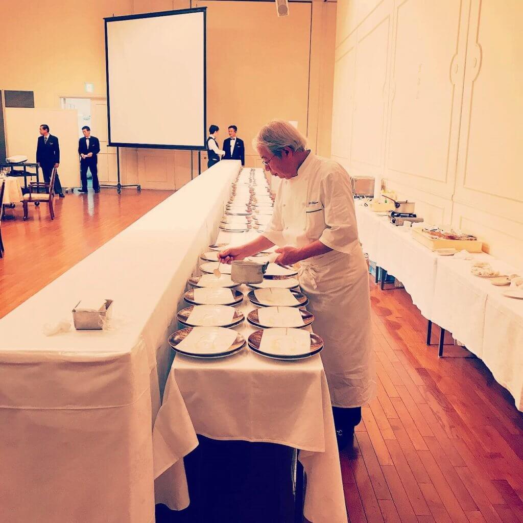 会場内の特設キッチンで次の料理の準備をするシェフ